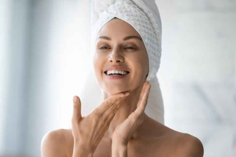 Happy woman with her hair wrapped in a towel looking at her liquid facelift results in the bathroom mirror.